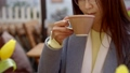 Close-up of a charming brunette asian woman sitting in a cafe and drinking coffee. 49648748
