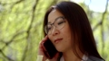 Close-up portrait of a lovely brunette woman in glasses talking over the phone outdoor. 49648963