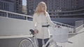Pretty blond smiling woman in warm white jacket standing at the city street with bicycle looking in 49649103