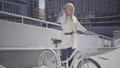 Pretty blond woman in warm white jacket standing at the city street with bicycle looking in the 49649106