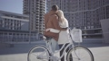 Tall man hugs pretty blond woman in warm jacket standing near bicycle looking on the high building 49649125