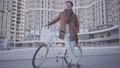 Handsome serious man in brown coat and light blue jeans standing with his bicycle in the city in 49649129