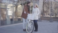 Tall man holding his bicycle talking with pretty blond woman in warm jacket. Positive couple 49649141