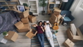 Happy couple taking things from box lying on carpet relaxing during relocation 49679041