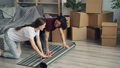 Happy girl and guy unrolling carpet at home and talking then lying relaxing 49679067