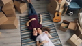 Top view of happy man and woman talking lying on carpet in new flat with boxes 49679070