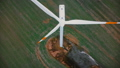 Drone flying very close up to working windmill turbine with red stripes, alternative ecological 49681567