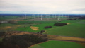 Scenic aerial panoramic view of large windmill turbine farm generating power in autumn field, eco 49681832