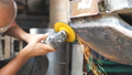 Adult welder polishing auto with electric professional equipment in garage. Male repairman or 49688737