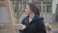 Successful beautiful young girl painter sitting in front of wooden easel looking around. Female 49689298