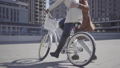 Handsome man in brown coat teaching his girlfriend to ride the bicycle in the city, both people 49689314