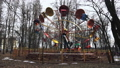 A carousel with sitting people rotates in a circle. It is located in the city park. It it early 49730921
