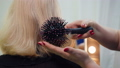 Hairdresser puts hair with a comb for senior lady sitting before the mirror. 49750722