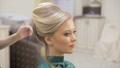 Hair master sprays varnish, makes curls, blonde, beauty salon, slow motion 49752827