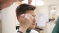 Hairdresser's hands at working process. Barber making haircut of attractive man in Beauty saloon 49752837