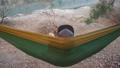man riding a hammock looking at the lake 49769698