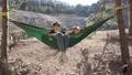 girl lying with a boy on a hammock, a boy swinging 49769712