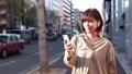 スマホで音楽を聴きながら歩く女性 49802211