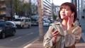 スマホで音楽を聴きながら歩く女性 49817736
