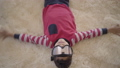 Portrait of adorable african american boy lying on the floor on the beige fluffy carpet with ski 49852988