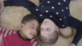 Portrait cute african american boy and blond caucasian girl lying on the floor on the beige fluffy 49853009
