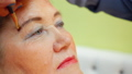 Face elderly woman while eyebrows makeup in beauty studio close up 49890714