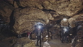 A couple of speleologists are exploring a cave. 49925145