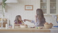 Cute mother and pretty daughter chatting while sitting at the Easter table with a basket and Easter 49956325