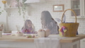 Pretty mom and cute daughter chatting while sitting at the Easter table with a basket and Easter 49956327