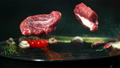Super slow motion of falling raw beef steaks on gr 50056274
