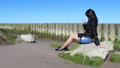 young woman sitting on a stone by the sea 50062409