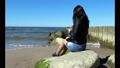 young woman sitting on a stone by the sea 50062410
