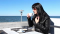young woman drinking coffee in an outdoor cafe 50062411