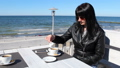 young woman pouring milk in coffee 50062415