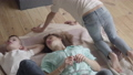 Young mother with her teen sons lying on the floor in children's room talking, sharing 50073717
