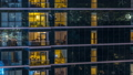 Glowing apartment windows at night in glass skyscraper timelapse 50085261