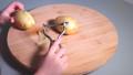 Hands of little girl peeling potatoes with peeler on wooden desk 50085862