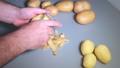 Man's hands peeling potatoes with kitchen peeler 50085867