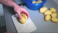 Man's hands holding a knife and cutting potatoes into slices 50085869