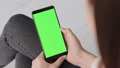 Chroma Key Mockup with Green Screen on Mobile Phone of Young Woman at Home 50091641
