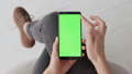 Chroma Key Mockup with Green Screen on Mobile Phone of Young Woman at Home 50091647