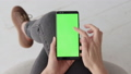 Green Screen on Mobile Smartphone of Young Woman at Home for Chroma Key 50091650