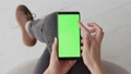 Green Screen on Mobile Smart Phone of Young Woman at Home for Chroma Key 50091672