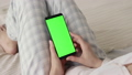 Green Screen on Mobile Phone of Young Woman in Bed at Home for Chroma Key 50091675