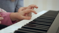 Young woman teaches little girl to play the piano. 50092099