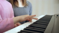 Young woman teaches little girl to play the piano. 50092100