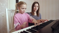 Young woman teaches little girl to play the piano. 50092104