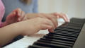 Young woman teaches little girl to play the piano. 50092105