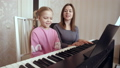 Young woman teaches little girl to play the piano. 50092110