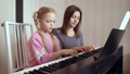 Young woman teaches little girl to play the piano. 50092116